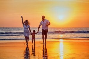 Family walking on beach with setting sun