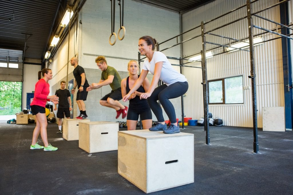 Male and female athletes doing box jumps at gym