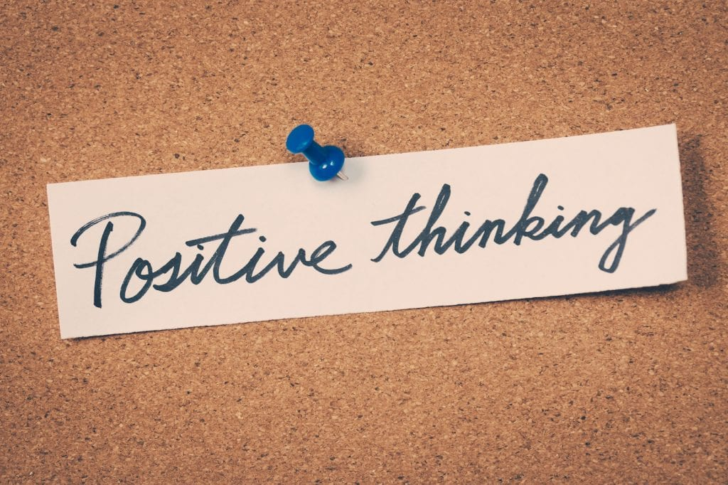 Positive thinking written in cursive pinned on a cork board