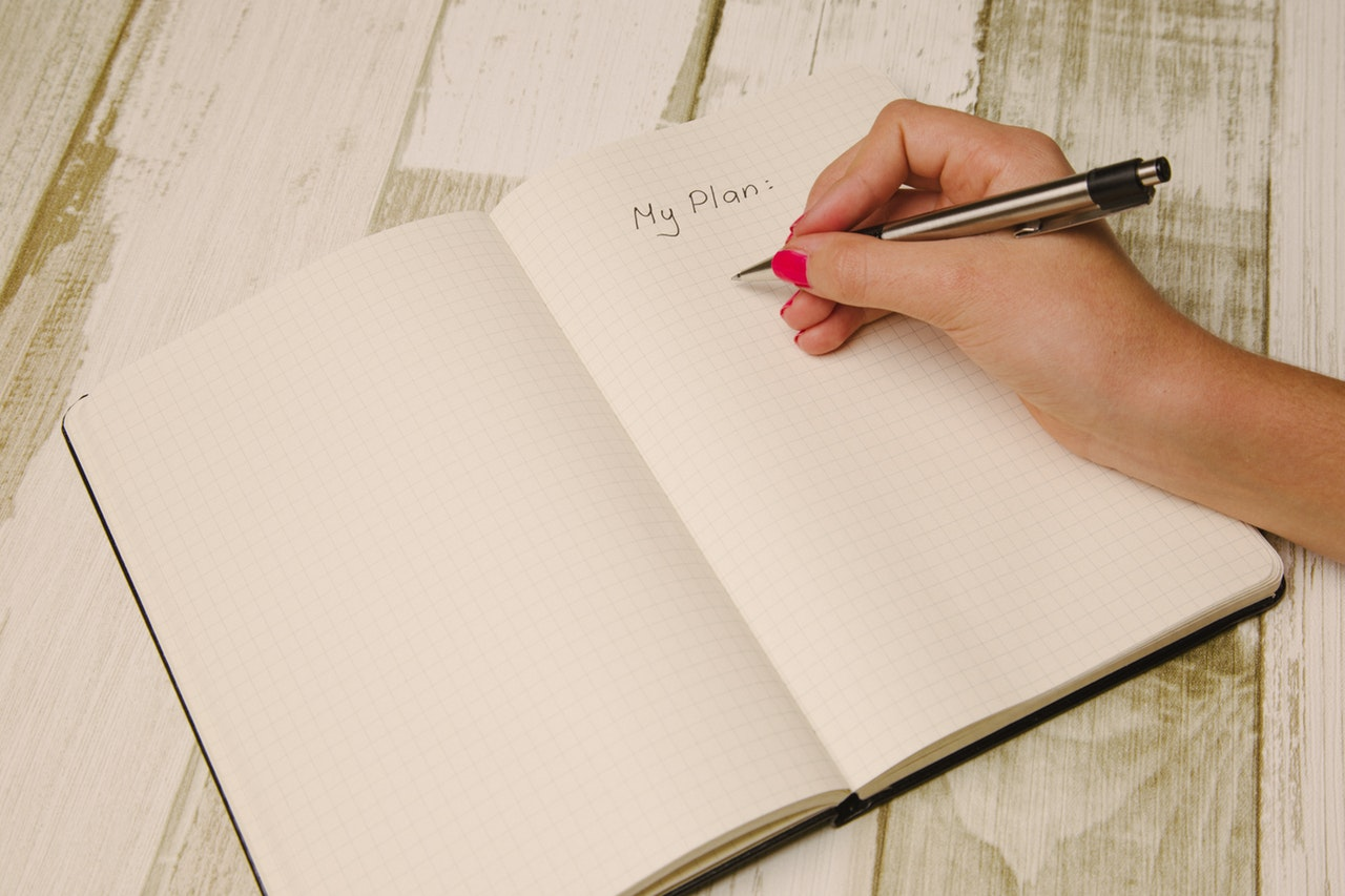 person writing her plan on a notebook