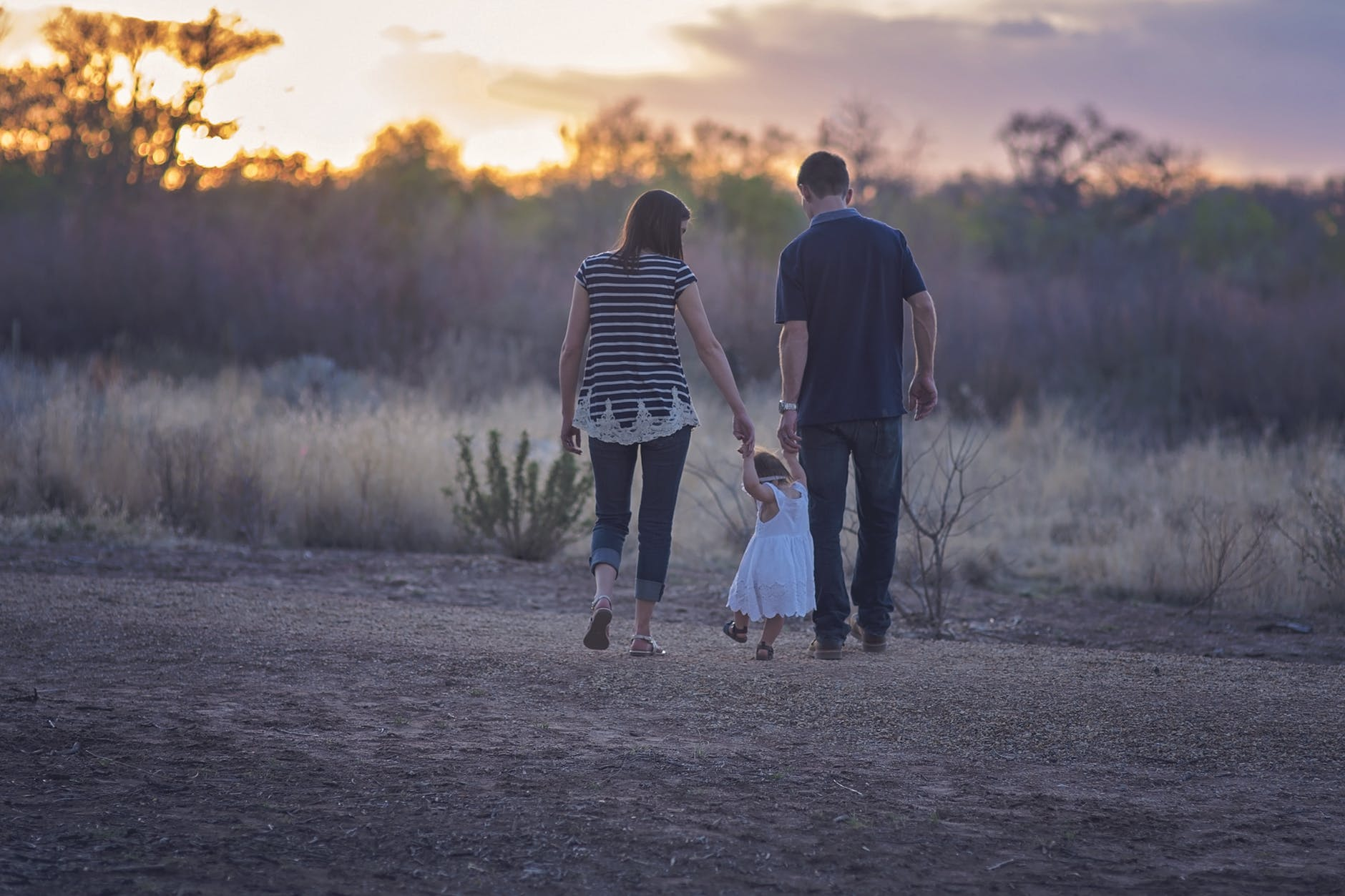 Family of three walking on grassy field